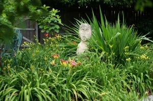 The Garden Lady stands sentinel in the day lily bed.