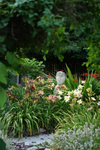 The Garden Lady is framed in day lilies and crocosmia.  The is the view from the entrance of the Secret Garden.