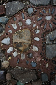 My wonderful neighbors brought the large center stone back from a trip out east where it sat in a stream that ran below a wooden covered bridge.  It is now at the entrance of the Secret Garden.  Surrounding it are Petoskey Stones that I picked up on a beach in Leland, Michigan.