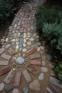 This little medallion marks the spot where the two paths in the Secret Garden diverge. At the top is the entrance to the garden.