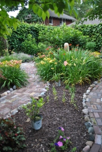 Rosie Returns day lily on the left, First Knight is the yellow lily across the path, crocosmia near the garden lady.